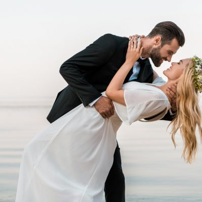 affectionate wedding couple going to kiss on beach