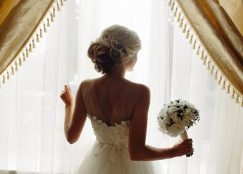 beautiful bride in a traditional white wedding dress, standing by window.