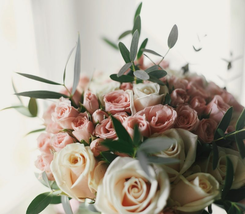 beautiful gentle wedding bouquet with big and little pink roses with greenery  in morning light. stylish wedding adorning and arrangement