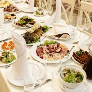 stylish fashionable decorated table with flowers and delicious food, celebration wedding, catering in the restaurant