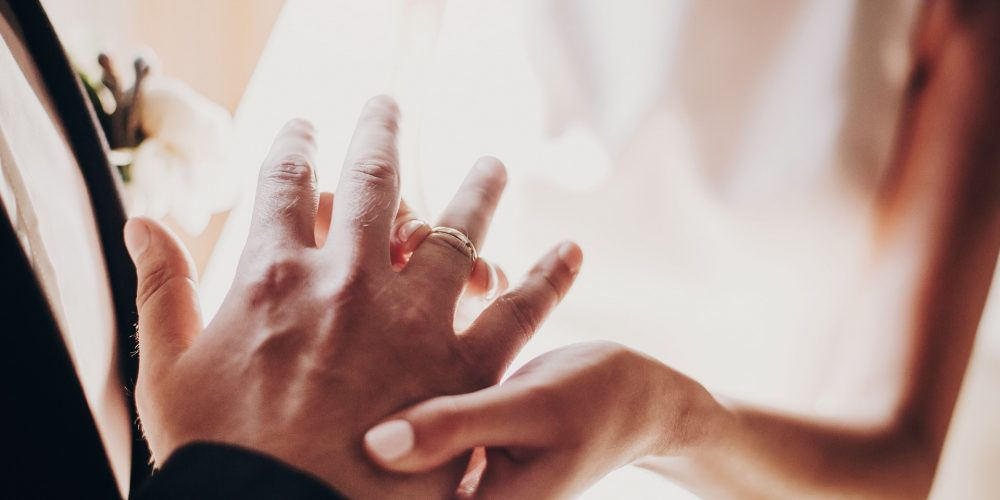 Wedding couple exchanging wedding rings during holy matrimony in church. Bride and groom putting golden rings on finger, close up. Spiritual moment